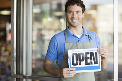 "Business owner holding ""Open"" sign"